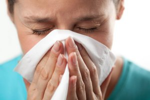 Woman sneezing into tissue