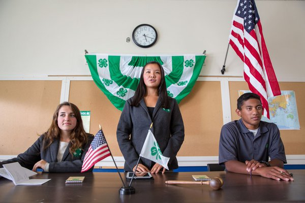 Three 4-H club officers holding a meeting.